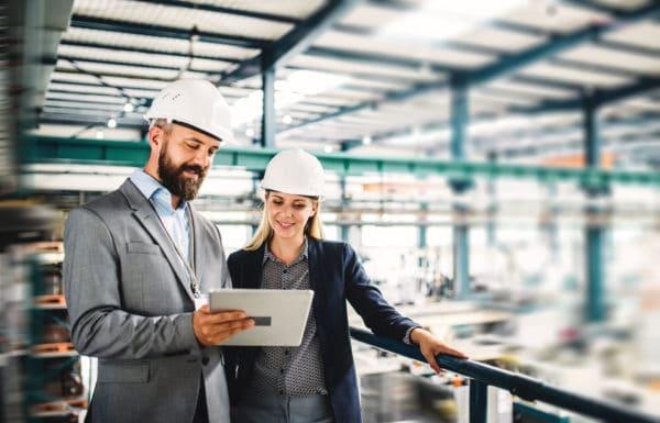 deux personnes regardent une tablette dans un entrepôt pour un audit