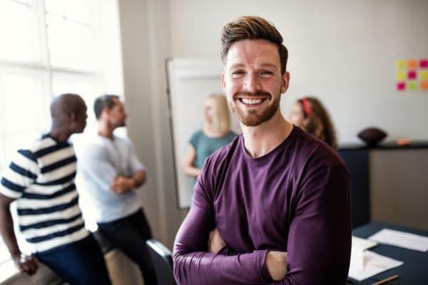 un homme au premier plan avec un grand sourire et 4 personnes en réunion brainstorming derrière