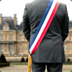le dos d'un homme avec son écharpe de maire et le bâtiment d'un mairie en fond